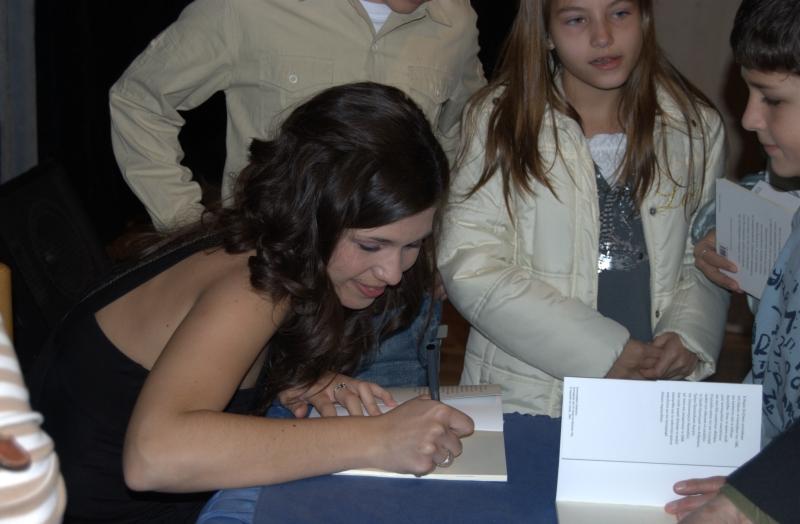 Η Μαρία Χατζίκου υπογράφει τα βιβλία όσων παρεβρ�θησαν στην εκδήλωση.